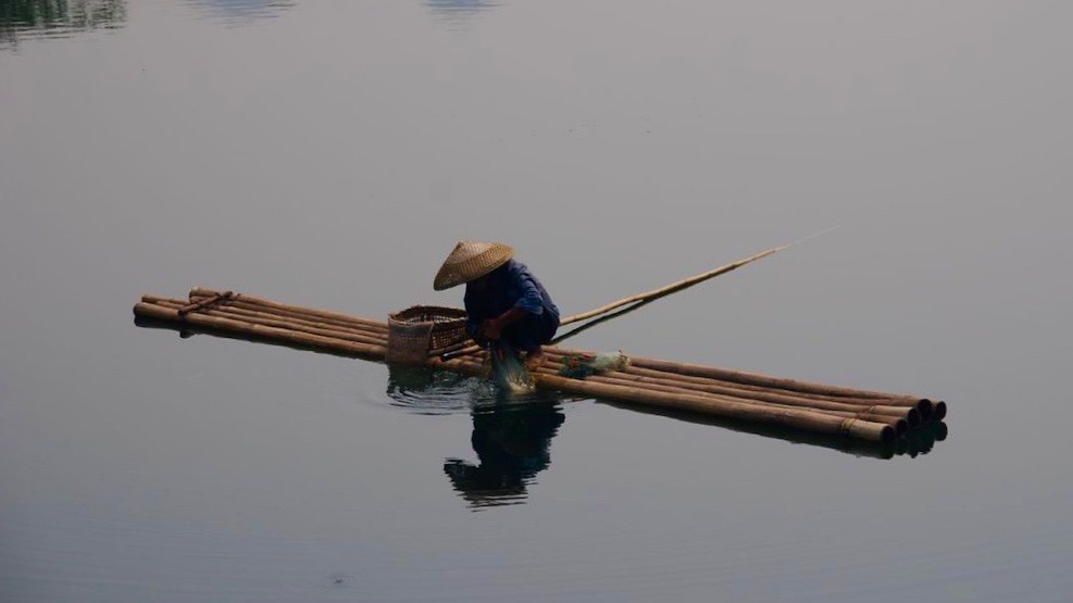 Fisherman on bambooboat China